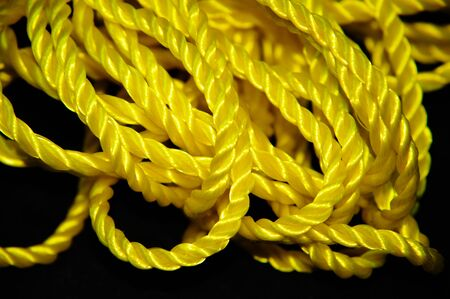 Yellow Rope with Curls and Folds on Black Background Stock Photo - 17574556