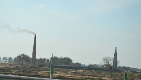 brick kiln: Two Smoking Brick Kiln Chimneys