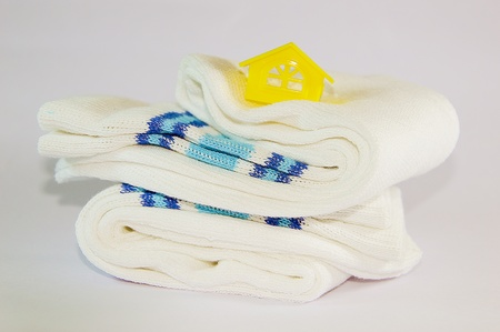 A symbol of home placed on the top of two socks  Showing the comfort of home of fine fabric   photo
