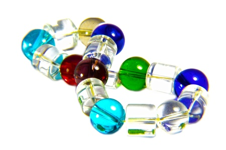 Different colors of glass beads used in a bracelet  Transparent beads isolated on white background  photo