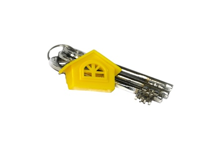 Three keys and yellow home isolated on white background. photo
