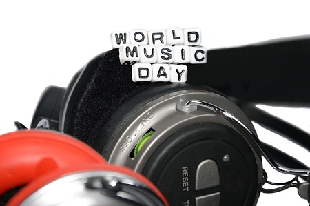 World music day on top of two headphones.  The blocks are resting on earphones photo