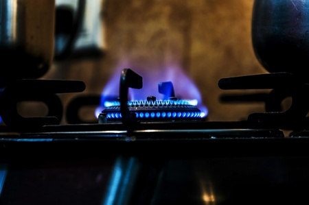 Kitchen gas stove burner having blue flame  The natural fire with blue colors   photo