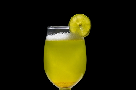 Mixed margarita drink in transparent glass with slice of lime on black background   photo