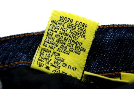 Yellow tag attached with the jeans informs washing instructions and guides   photo