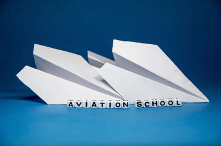 Aviation school conceptual idea with paper planes and letters of alphabets on blue background   photo