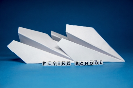 Concept of flying school with letters, blocks and paper planes on blue background   photo