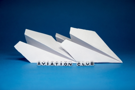Aviation club concept with letters and paper planes on blue background  photo
