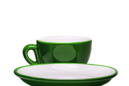 Green cup and saucer on white background   photo