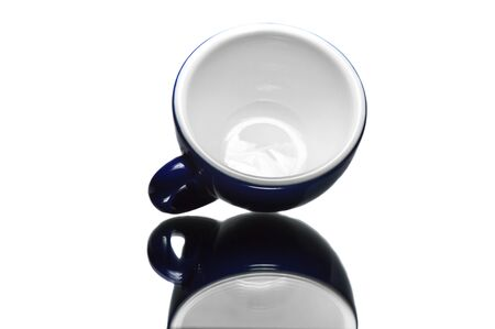 Empty blue cup on reflective surface and white background   photo