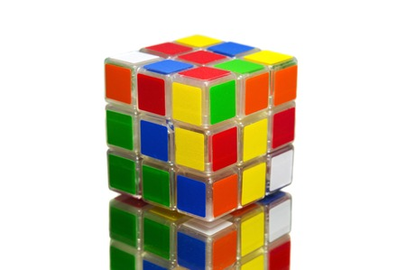 unsolved: Rubiks cube on white background and reflective surface