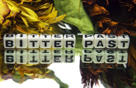 Bitter past with wilted flowers on white background  It also contains text message,  photo