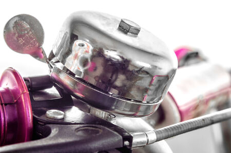 handlebar: Shiny white metal bell on handlebar or bicycle.