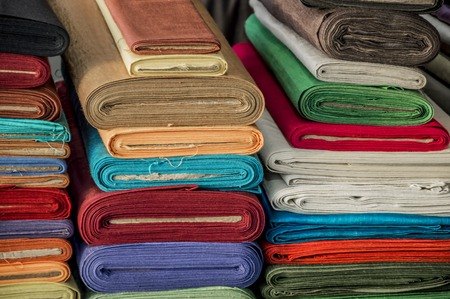 Various colorful rolls of fabric. Stock Photo
