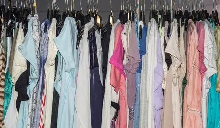 differnt: Shirts for women on sale at shop. Differnt colored dresses hanging in row.