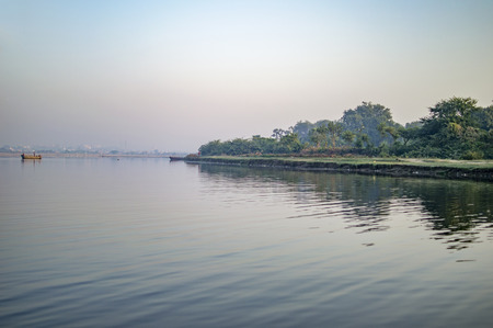 river banks: Boat and river banks with forest and blue water morning times.