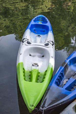 Two kayak boats of fibreglass are empty and at the side of the water.