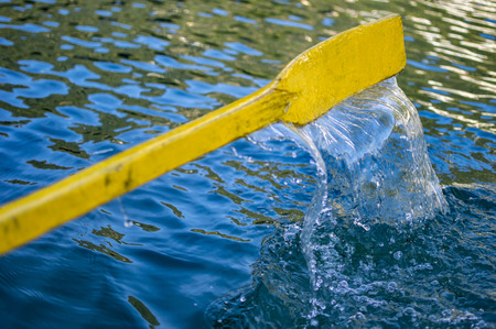 Yellow oar of boat in dark water which is dripping from it.