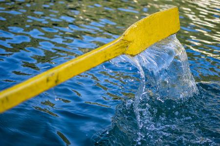 falling tide: Yellow oar of boat in dark water which is dripping from it.