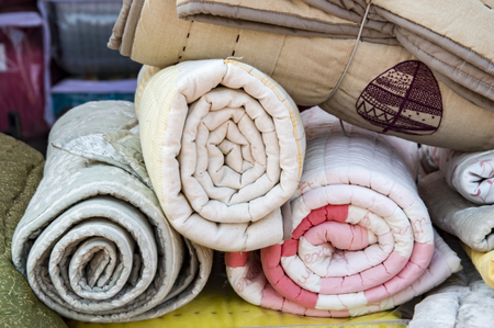bedspread: Rolled quilts on display and sale at a shop. Stock Photo