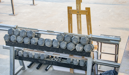 dumb bells: Dumbbells and other excerise equipments placed on a rack. Stock Photo