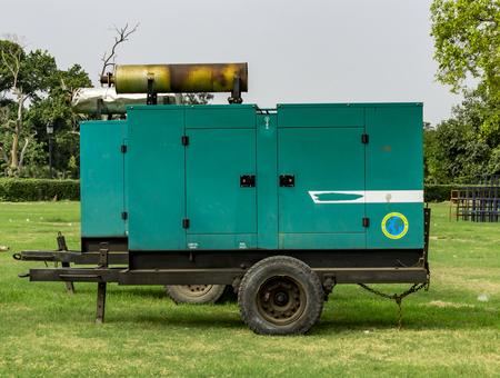 outage power: Power generator in the field of green grass and trees.