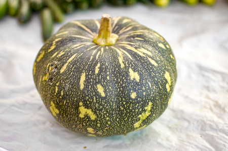 Green and yellow pumpkin on ground for sale