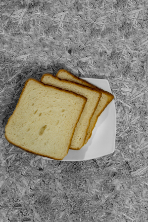 Bread pieces and slices in white plate on rugged surface