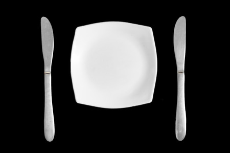 Two stainless steel knives and a white plate on black