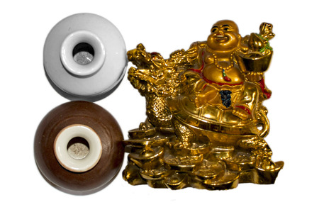 Two pots and golden laughing buddha on white surface