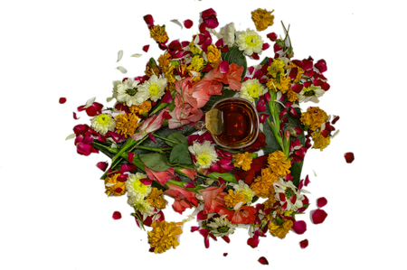 Tea cup with liquid and other flowers and leaves surrounding