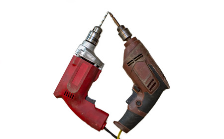 Two different colored drill machines on white surface