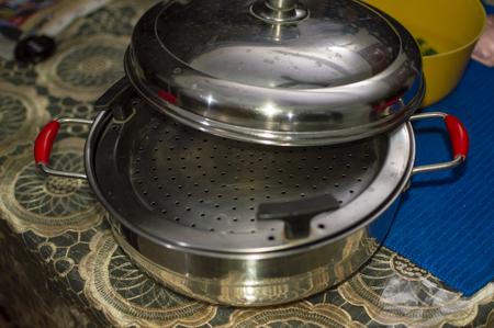 Vegetable steamer on table with lid and side handles