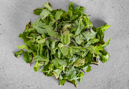 Heap of peppermint leaves and grass on white surface
