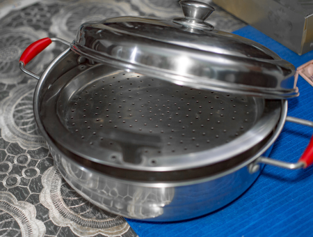 Two lids of vegetable steamer and on blue cloth on the table