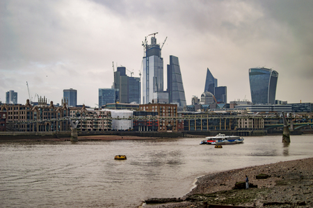 The big tall buildings across the river thames and mud
