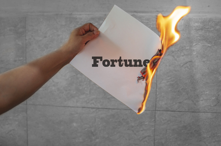 Burn fortune text on burning paper in the hand