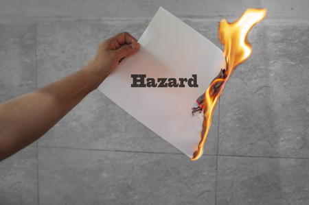 Hazard text on burning paper in the hand