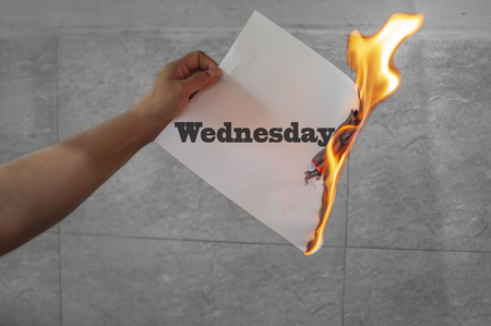 Wednsday word text on fire with burning paper in hand