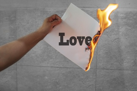 Love text burning on paper in hand