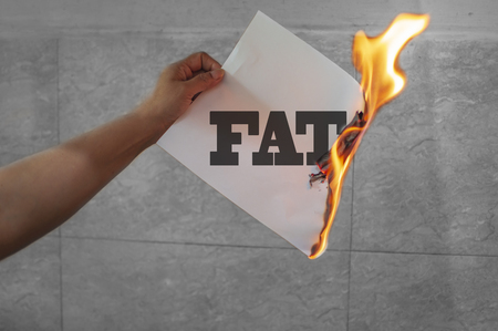 Burn fat text on burning paper in the hand
