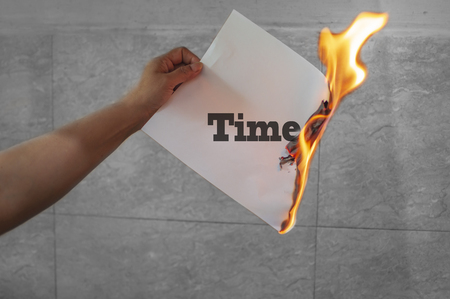 Time word text on fire with burning paper in hands