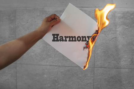 Burning harmony text on paper with flame in hand