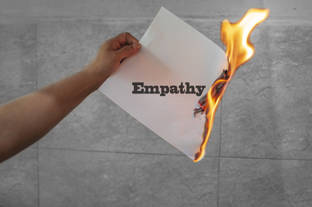 Empathy text on burning paper in the hand
