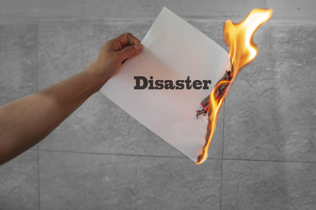 Disaster text on burning white paper in the hand of a female. Stock Photo