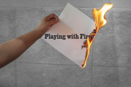 Playing with fire words text on fire with burning paper in hand Stock Photo