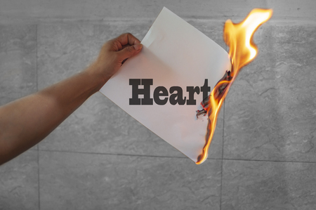 Heart burn text on burning paper in hand Stock Photo