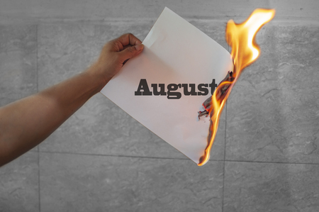 August word text on fire with burning paper in hand
