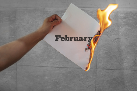February word text on fire with burning paper in hands Standard-Bild