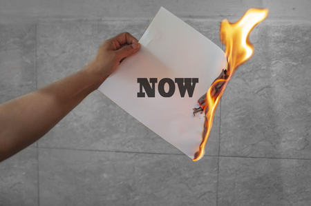 Now word text on fire with paper burning in hand